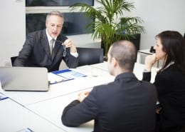 Man talking to man and woman at meeting