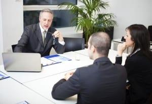Man talking to man and woman at meeting